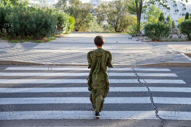 Rear view of a boy wearing a space suit- crossing road- zebra crossing