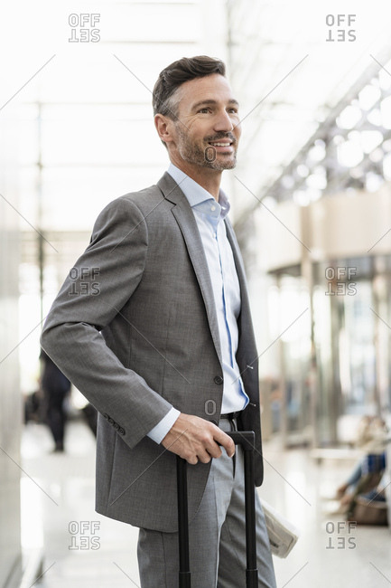Portrait of smiling businessman with baggage