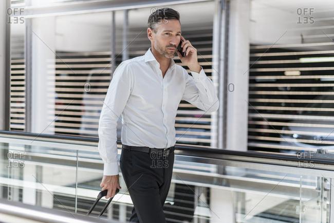 Businessman on escalator talking on the phone
