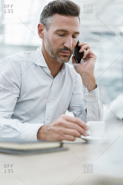 Portrait of businessman in a cafe talking on the phone