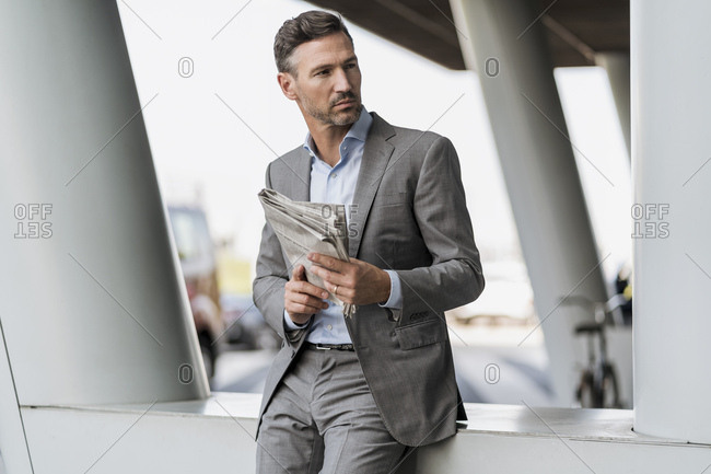 Portrait of businessman with newspaper outdoors