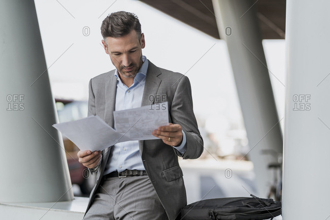 Businessman reviewing papers outdoors