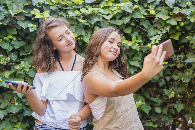 Young girls taking a selfie on ivy background
