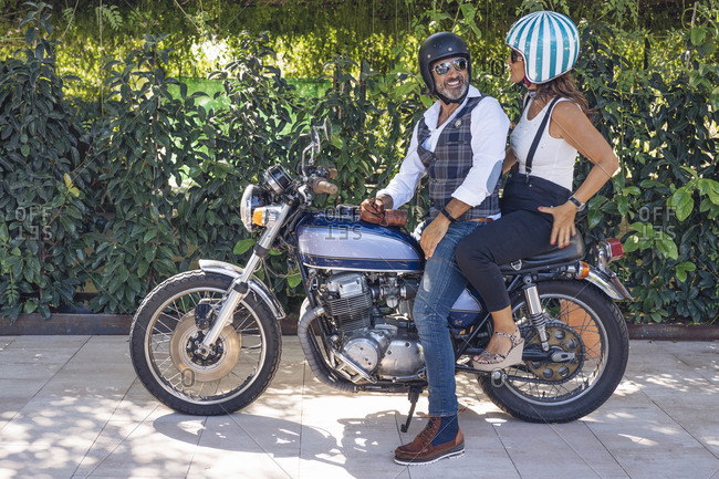 Happy mature couple on a vintage motorbike