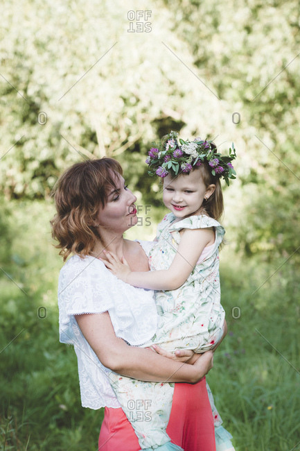 Mother holding daughter with flower wreath