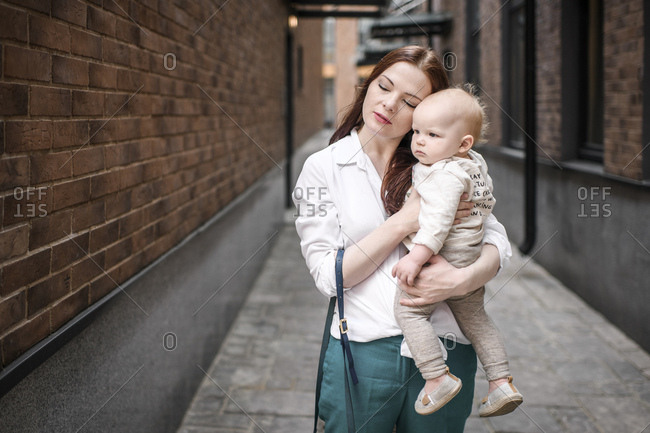 Mother holding her baby boy in an alley