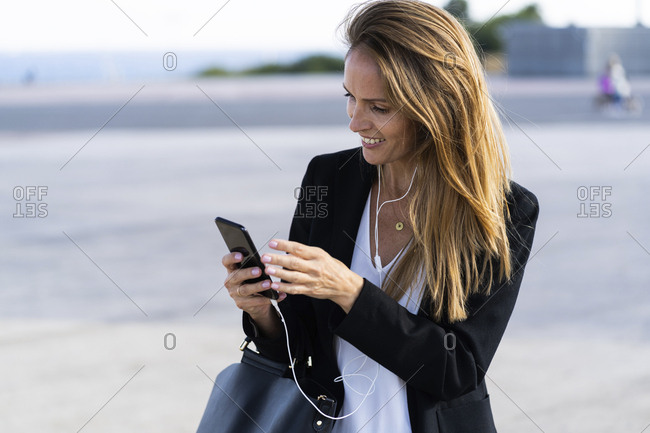 Smiling businesswoman with smartphone and earphones outdoors