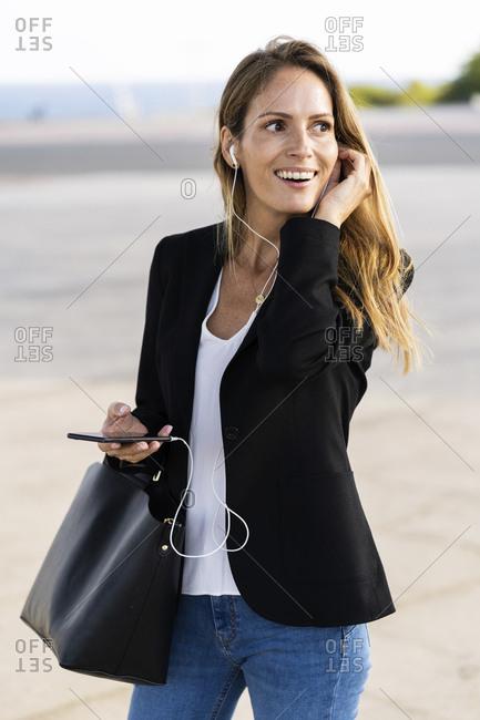 Happy businesswoman with smartphone and earphones outdoors