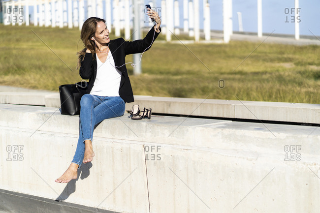 Smiling businesswoman sitting on a wall with smartphone and earphones