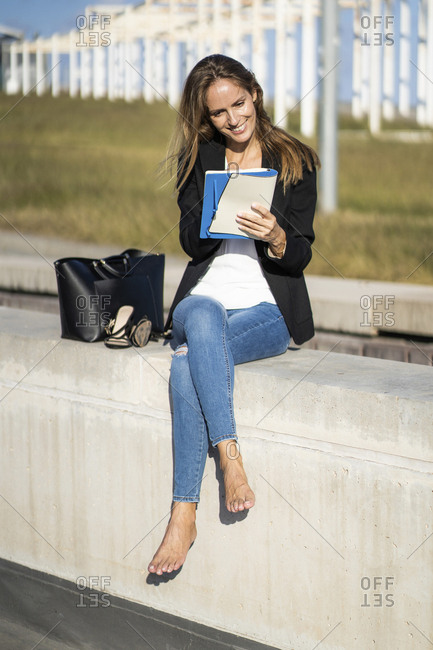 Smiling businesswoman sitting on a wall with a notebook