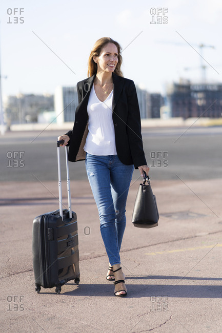 Smiling businesswoman with baggage on the go