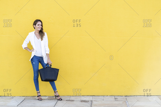 Smiling woman standing at a yellow wall holding a handbag