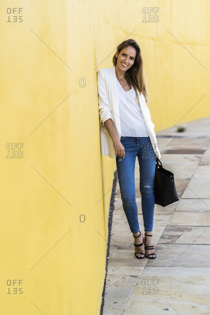 Portrait of smiling woman standing at a yellow wall holding a handbag