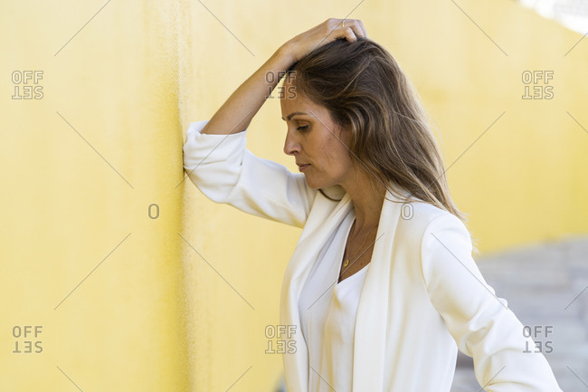 Desperate woman leaning against a yellow wall