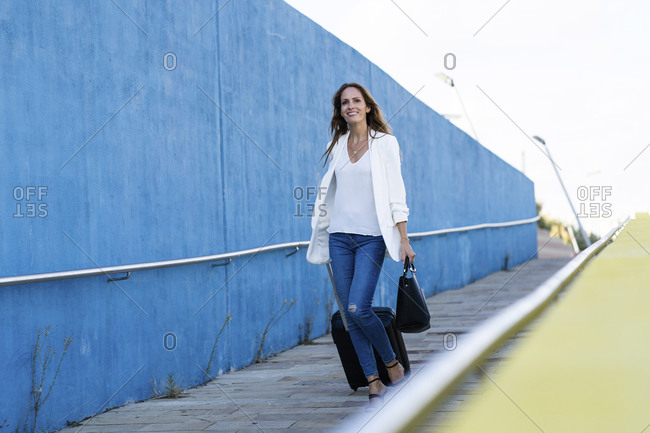 Businesswoman with baggage walking along blue wall