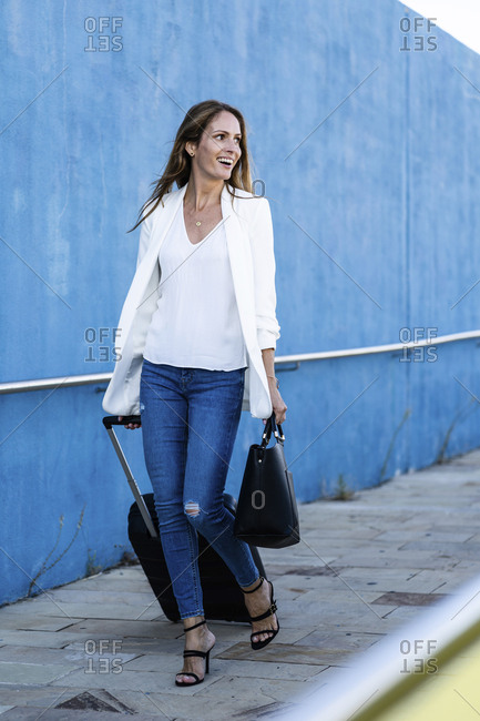 Happy businesswoman with baggage walking along blue wall
