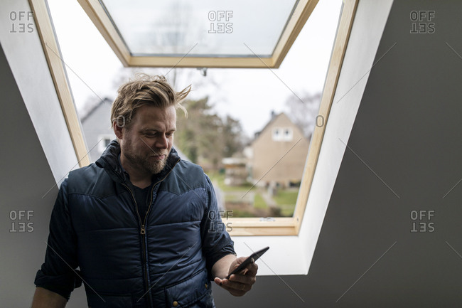 Architect reading message on his mobile phone