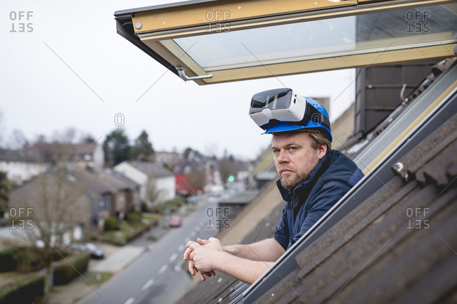 Architect with VR goggles on his safety helmet- looking out of roof light