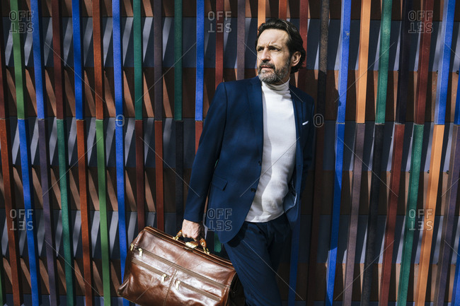 Portrait of mature businessman with leather briefcase watching something