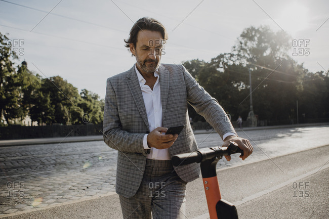 Businessman looking on smartphone holding e-scooter in the city