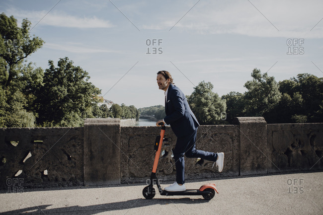 Businessman with e-scooter on a bridge
