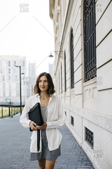 Well dressed woman carrying folder- walking in the city