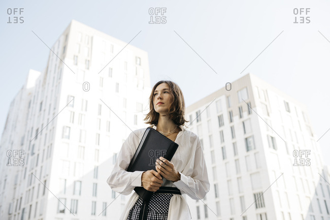 Serious woman carrying folder in the city