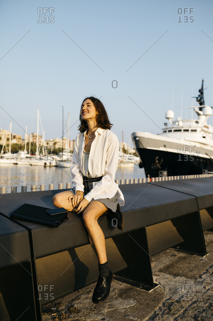 Pretty businesswoman sitting at the marina after work- relaxing
