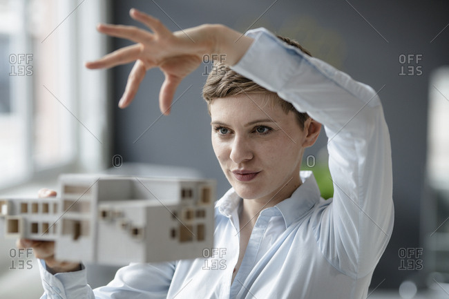 Confident businesswoman holding architectural model in office