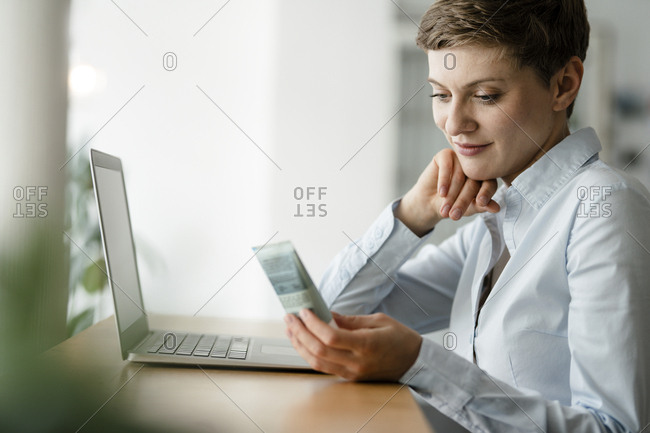 Businesswoman with laptop holding cream tube