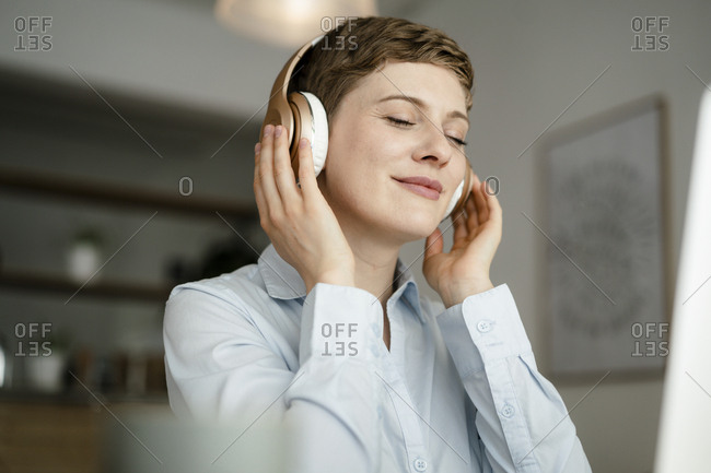 Portrait of businesswoman listening to music with headphones
