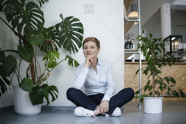 Portrait of a businesswoman sitting on the floor surrounded by plants