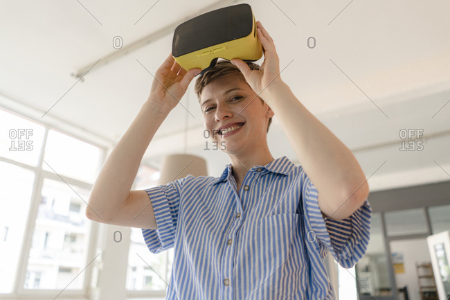 Portrait of smiling businesswoman with VR glasses in office