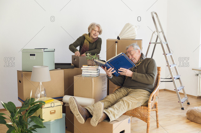 Senior couple with photo album surrounded by cardboard boxes in an empty room