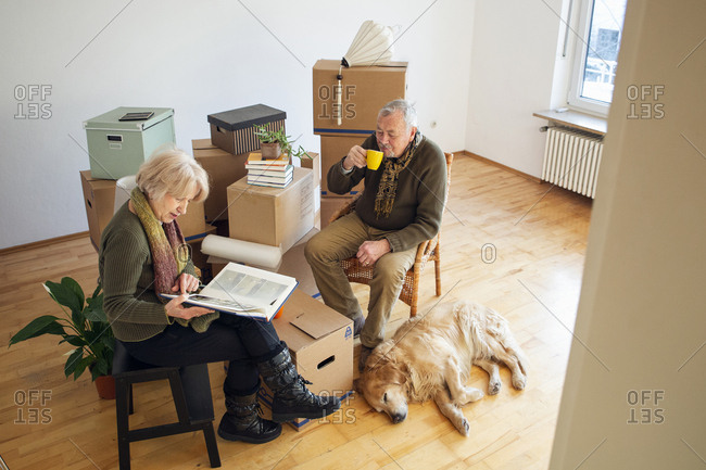 Senior couple having a break surrounded by cardboard boxes in an empty room