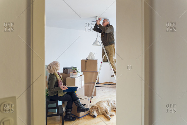 Senior couple in a new home with man mounting ceiling lamp