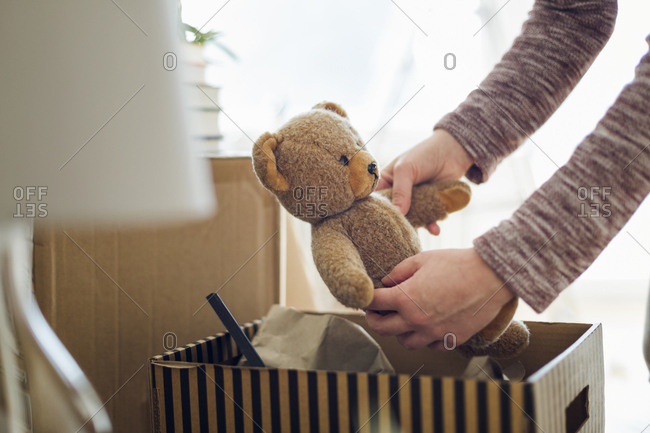 Close-up of woman unpacking cardboard box in new home taking out teddy bear