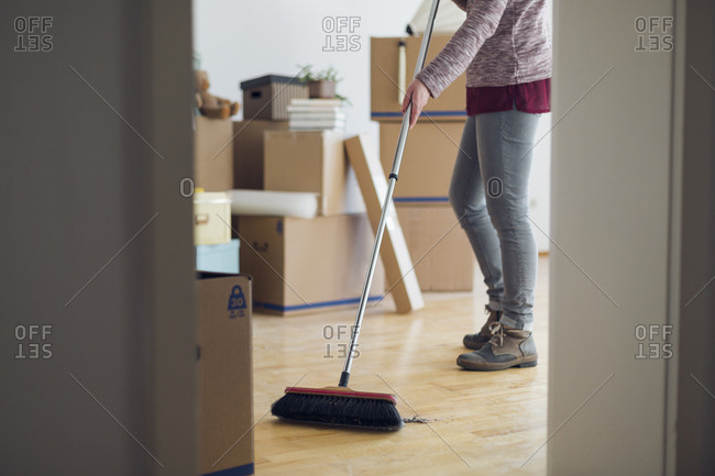 Woman sweeping the floor surrounded by cardboard boxes in an empty room