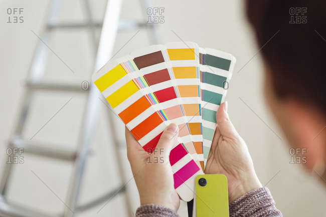 Woman holding color sample in an empty room with a ladder