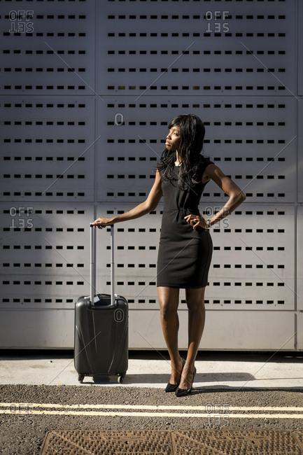 Businesswoman with trolley- looking sideways