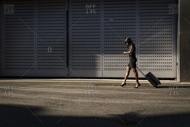 Businesswoman with trolley checking the time