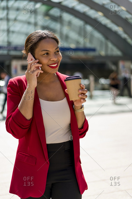 Portrait of smiling businesswoman with coffee to go on the phone- London- UK