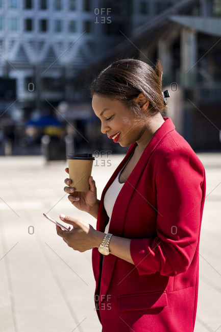 Smiling businesswoman with coffee to go looking at mobile phone- London- UK