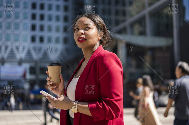 Portrait of businesswoman with coffee to go and cell phone- London- UK