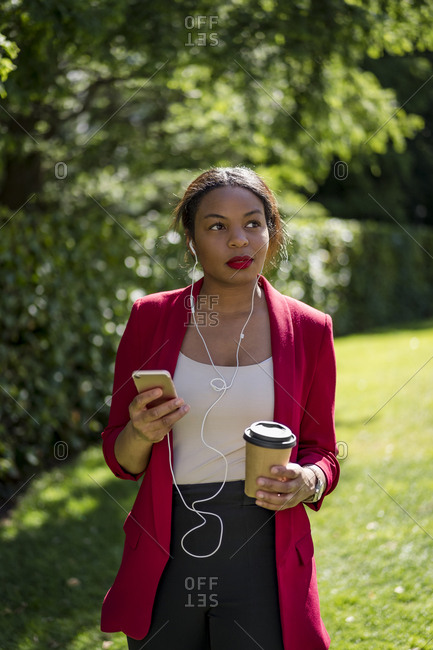 Portrait of businesswoman with coffee to go listening music with smartphone and earbuds- London- UK