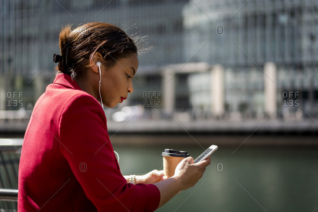 Profile of businesswoman with coffee to go using mobile phone and earbuds- London- UK