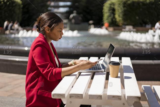 Businesswoman working on laptop outdoors- London- UK