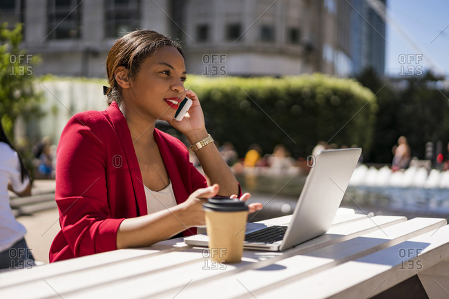Businesswoman on the phone with laptop and coffee to go outdoors- London- UK