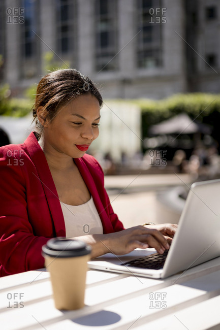 Portrait of smiling businesswoman working on laptop outdoors- London- UK