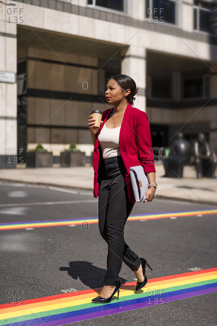 Businesswoman with coffee to go and laptop bag crossing the street on LGBT stripes- London- UK